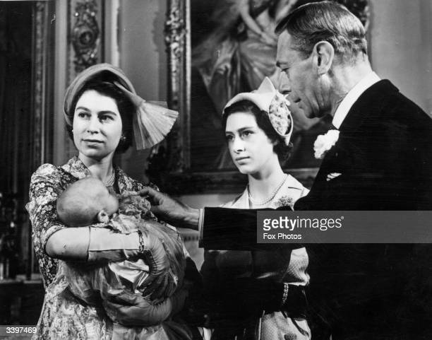 Princess Elizabeth holding her daughter Princess Anne on the occasion of her christening Looking on is her sister Princess Margaret and her father...