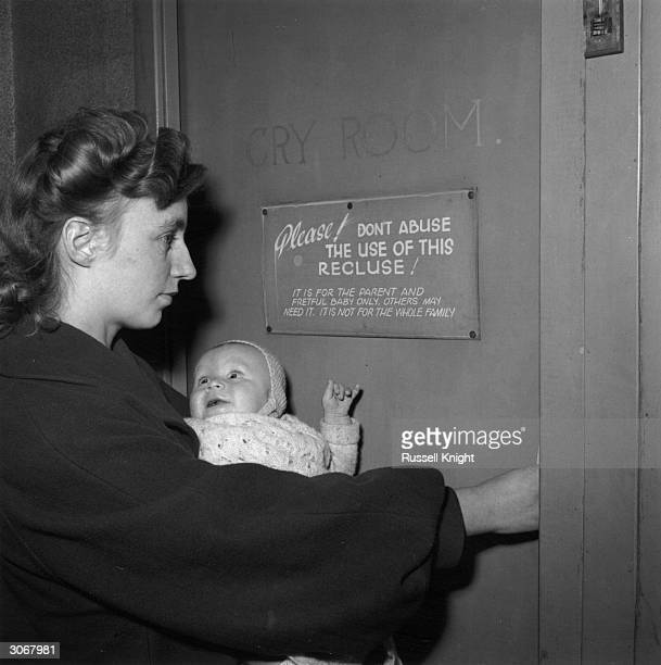 A mother takes her baby to the 'Cry Room' of the Western Talkie Theatre in Bradford Yorkshire where the infant can bawl without disturbing the rest...