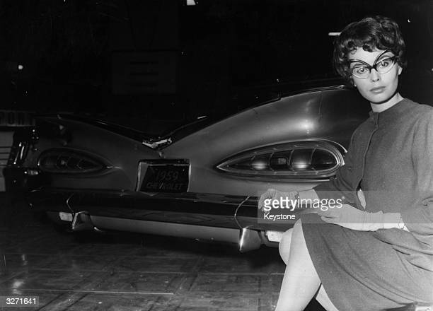 Model Angela Smith wears spectacles specially designed to match the rear styling of this 1959 Chevrolet Impala during the Motor Show at Earl's Court...