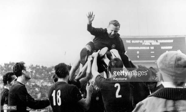 Members of the Hungarian football team toss their captain in the air after beating the Czech team in the football final at the Olympic Games Tokyo