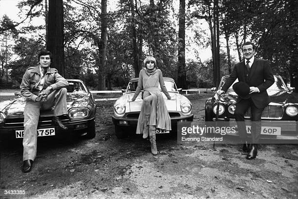British actors Gareth Hunt, Joanna Lumley and Patrick MacNee, the stars of the television series 'The New Avengers', sitting on the bonnets of their...