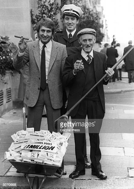 Littlewoods Pools winners Brian Carey a road tanker driver and Bertie Hemstock a retired roadsweeper smoking cigars outside the Grosvenor House Hotel...
