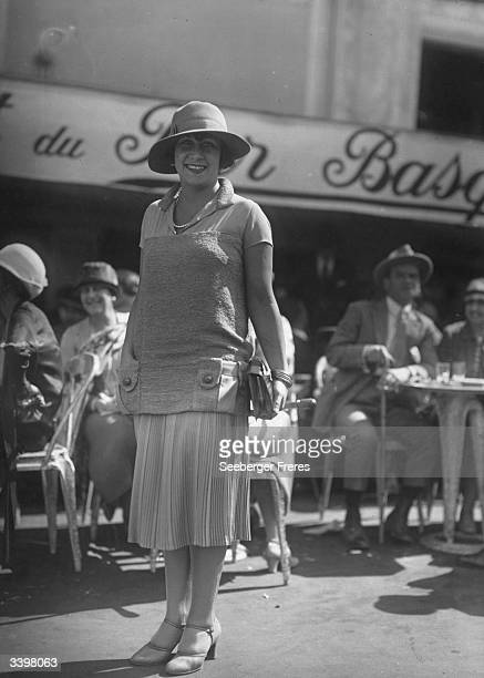 A woman wearing a pullover with a shirt collar and a pleated skirt outside a pavement cafe in Paris