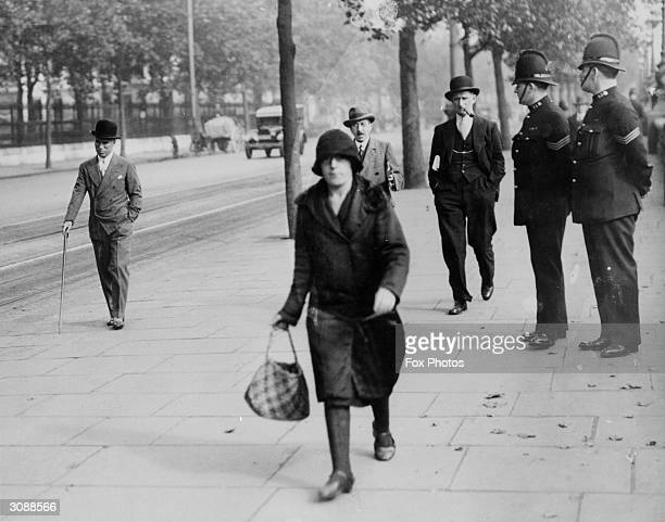 English comic actor director producer and composer Charlie Chaplin taking a stroll on London's Embankment watched by two policemen