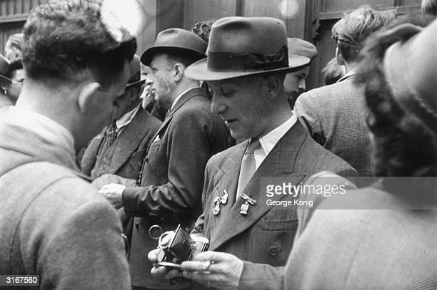 A man with a Voigtlander camera for sale on the blackmarket in London The brooches on his lapels are also for sale