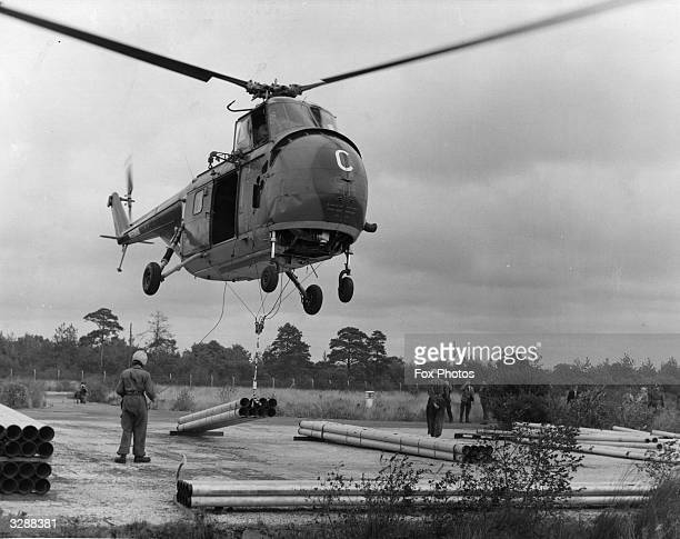 A Sikorsky S55 helicopter lifts eight twentyfoot sections of aluminium alloy piping before delivering them to 'forward areas' during a practical army...