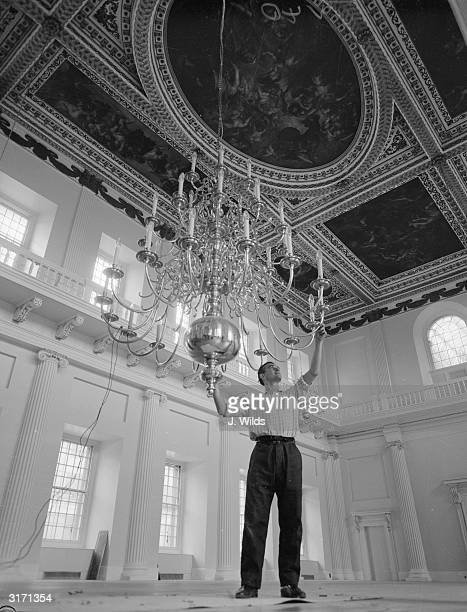 Fixing a chandelier in the newly-restored Banqueting House at Whitehall. The magnificent ceiling paintings overhead were commissioned by Charles I...