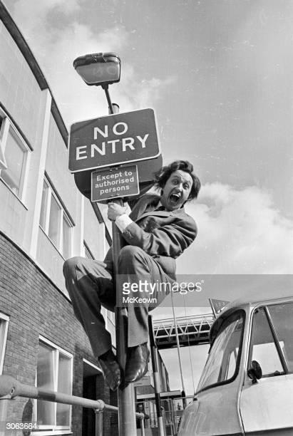 Bucktoothed Liverpudlian comedian Ken Dodd climbs up a 'No Entry' sign