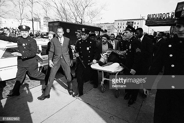 New York, NY- Two policemen carry stretcher bearing Negro nationalist leader Malcom X after he was downed by an assassin's bullets at a rally...