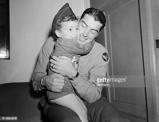 New York, NY: Loving embraces are exchanged by Staff Sergeant Joe DiMaggio, former slugging outfielder of the New York Yankees, and his son, three...