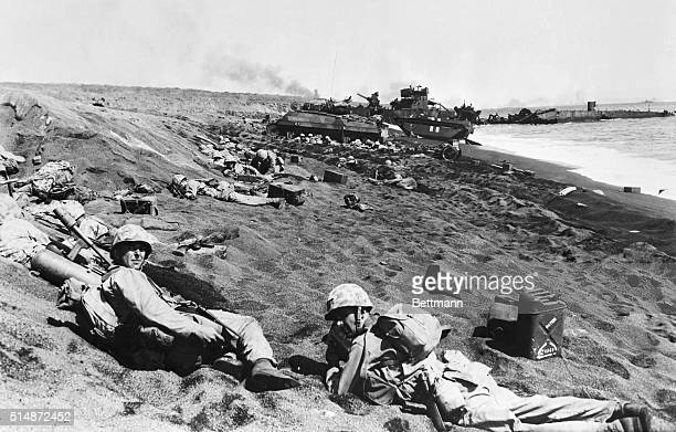Iwo Jima: The invasion search of Iwo Jima is littered with American equipment and Marines as Jap fire rakes the area. In background are wrecked hulls...