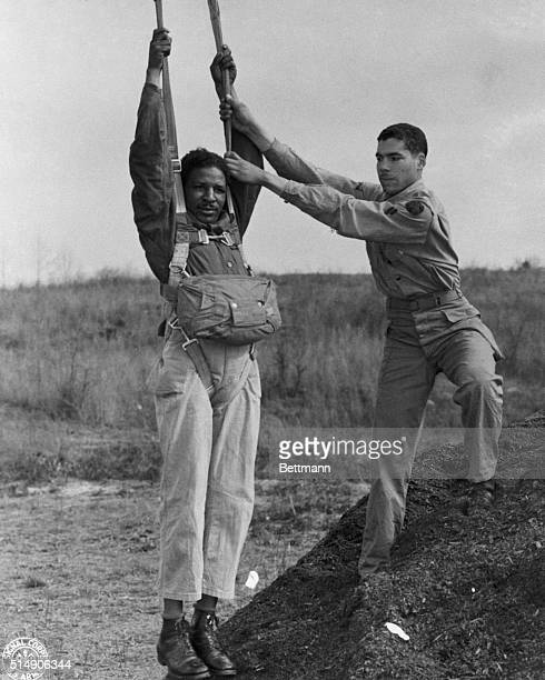 Fort Benning, GA- In training as to how to descend upon the enemy are these Negro paratroopers at Fort Benning. Landing from the mock tower in the...