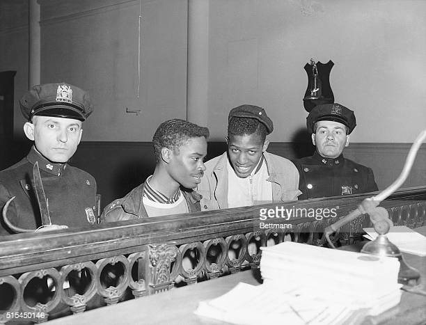 2/26/1958New York NY Vandie Merchison and Raymond Clark both of Brooklyn are flanked by patrolmen Mike Rosenbaum and Daniel Catalano as they are...