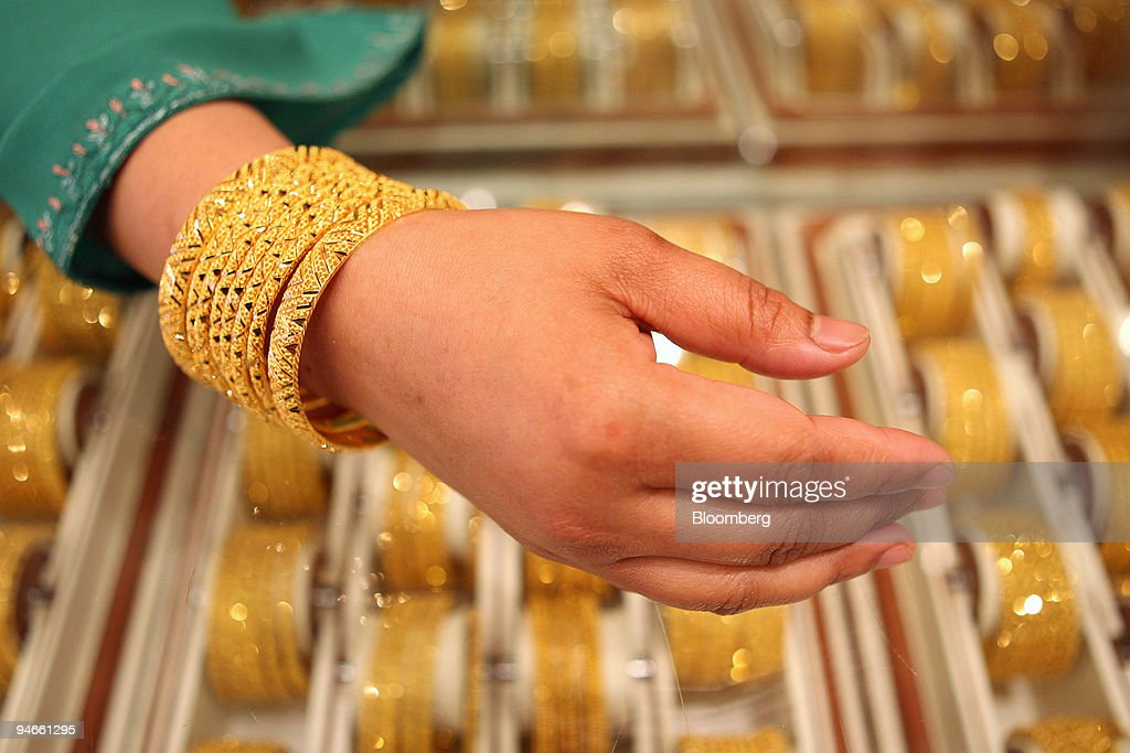22karat gold Bengal bracelets are displayed by a salesperso