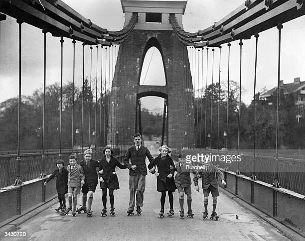 A group of schoolchildren rollerskating along the Clifton Suspension Bridge near Bristol
