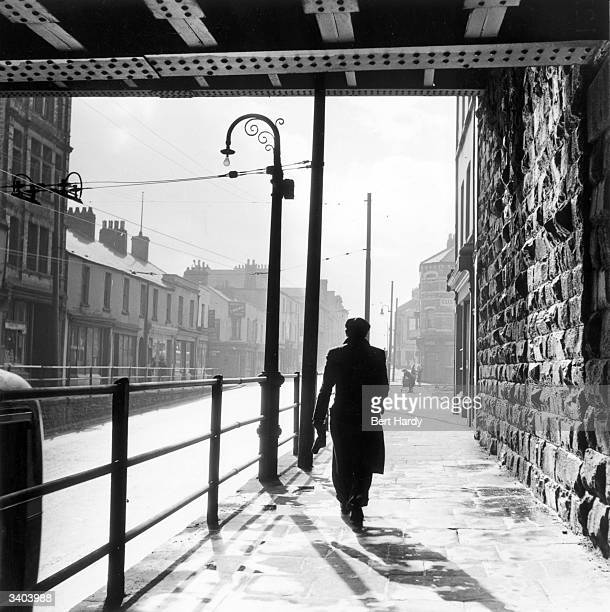 A man walking under a railway bridge in the dockland area of Cardiff known as Bute Town or Tiger Bay Original Publication Picture Post 5020 Down The...