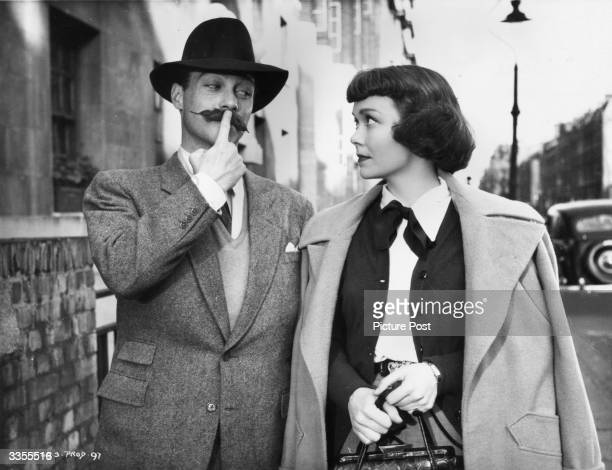 Irish actor Richard Todd fails to impress Jane Wyman with a false moustache during the filming of 'Stage Fright' directed by Alfred Hitchcock...