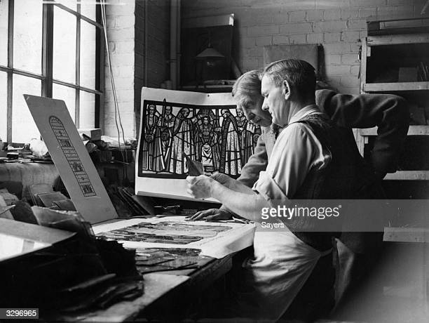 E Liddall Armitage chief designer and Arthur Howe head glass cutter working on a scene from the coronation being recreated in stained glass for the...