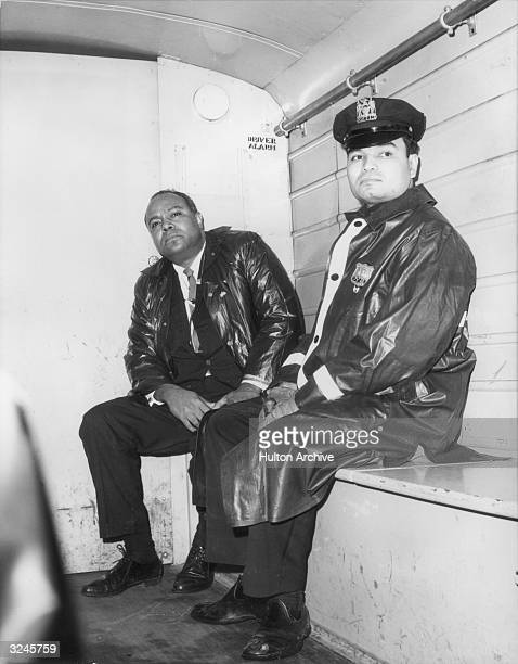 James Farmer the Executive Director of the Congress for Racial Equality sits next to a uniformed officer in the back of a police wagon following his...