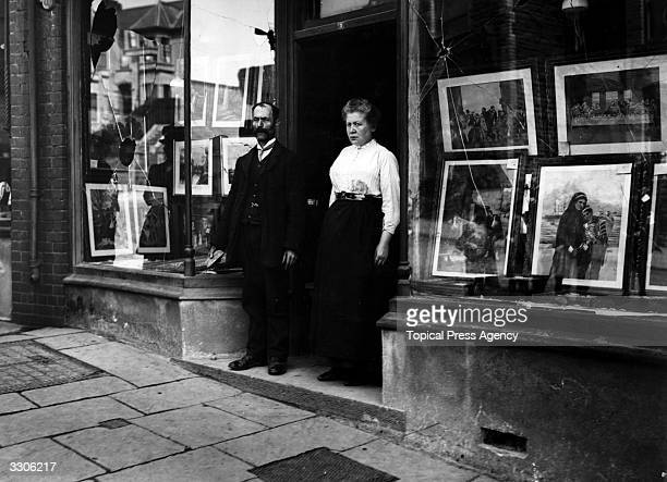 A couple stand in the doorway of their shop which has been vandalised as a result of antisemitic riots in Wales