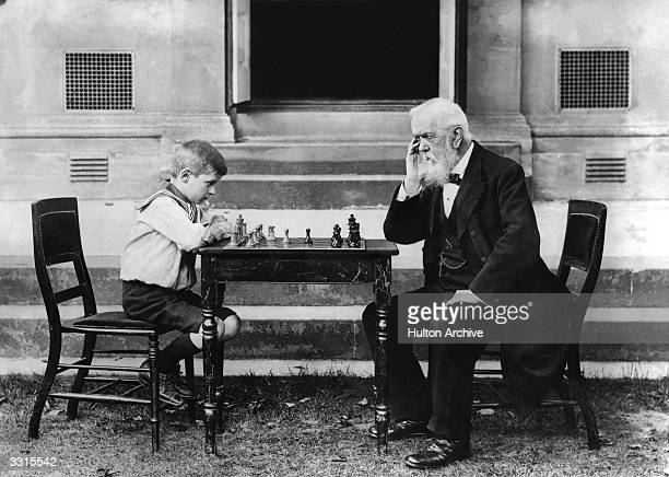 Walter Wisby, aged eight, playing a game of chess with T Whiltard, aged 91, in Cheltenham.