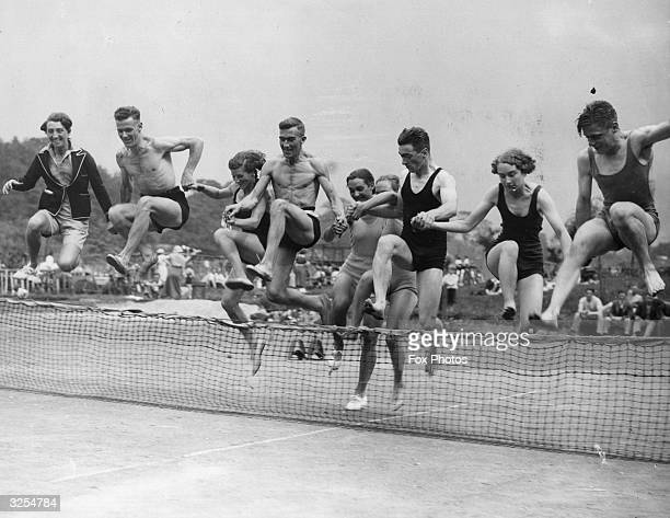 Sunbathers at the open air lido at Castle Mill Cheshire jump over the net on a nearby tennis court