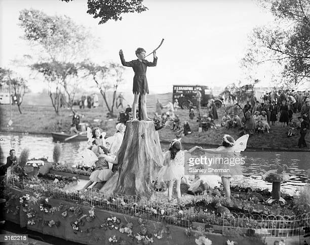 A boy dressed as Peter Pan surrounded by fairies floats down the river on a barge one of the attractions at the Hythe water Carnival in Kent