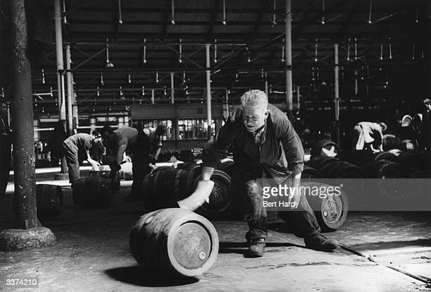 Paddy Farrell a worker at the Guinness brewery at Saint Jame's Gate Dublin rolling a full cask of ale in the racking shed ready for dispatch Original...