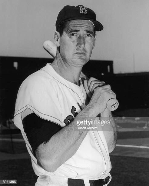 Halflength portrait of Boston Red Sox outfielder Ted Williams posing in uniform with a baseball bat celebrating Shriner's Day Fenway Park Boston...