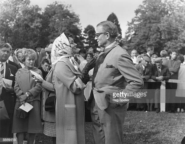 English actor and director Laurence Olivier with his actress wife Joan Plowright at Fontwell Park racecourse in Sussex