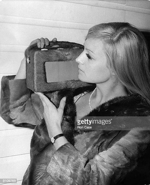 At a TV and Radio show in Earl's Court London model Louise Thomson wearing a pony skin coat and holding a portable radio made by Roberts Radio which...