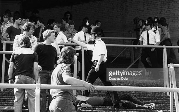 Police at the scene of a disturbance on the terraces during a football match between Millwall and Newcastle United