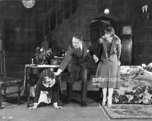 Actor Michael Sherbrooke grabs a chambermaid by the ear as he pulls her from her hiding place under the table in a scene from the play `Biddy'
