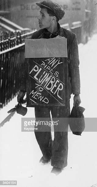 A plumber advertising his services on a sandwichboard as he walks a snowy street