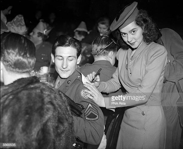 Jean Crawford uses the shoulder of Staff Sgt Bud Tyler of LaJunta Colorado to autograph his programme at the 25th annual Christmas Party of the Not...