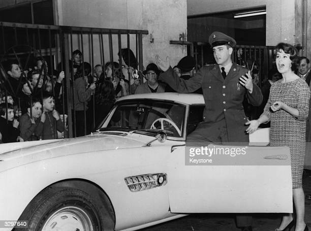 Fans watch as German TV celebrity Uschi Siebert presents American rock 'n' roll star Elvis Presley with the keys to the BMW sports car with which...