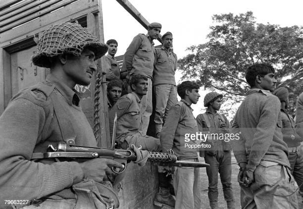 22nd December 1971, An Indian soldier with rifle and fixed bayonet watches over Pakistan prisoners captured during the Battle of Khulna, East...