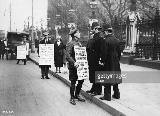 Police questioning sandwichboard carriers during a demonstration outside the Houses of Parliament in London at the time of the general strike