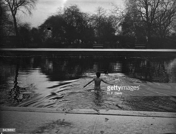 A 10 year old boy follows his father into the water at Victoria Park London for an early morning swim They are one of a group of hardy swimmers who...