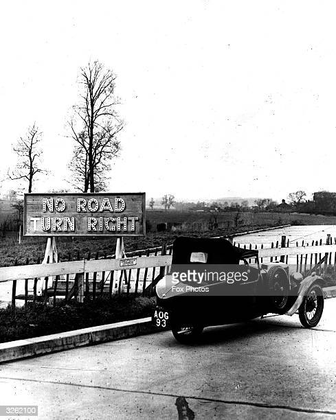 Three-wheeled car passes a sign where the London North Orbital road will be constructed at West Hyde Lodge near Rickmansworth.
