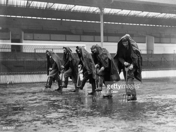 Tottenham Hotspur's ground staff drain a waterlogged goal area with pitch forks at White Hart Lane.