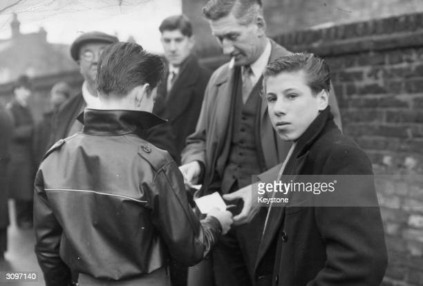 Fulham supporters buy 2 shilling tickets for 10 shillings outside the ground at Craven Cottage for the cup-tie match against Bristol Rovers.