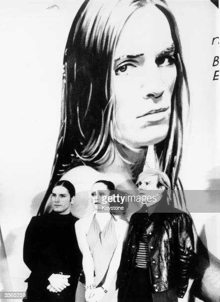 Pop Art's leading light Andy Warhol attends the German premiere of his film 'Trash' With him in front of one of the film's promotional posters are...
