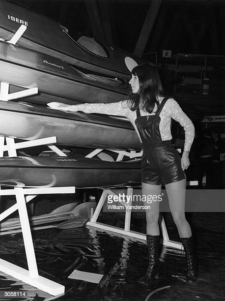 Saleswoman Jan McDougall a member of the Reading Kayak Club sells boats at a Canoe Exhibition in London wearing leatherlook hot pants