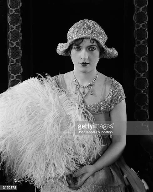 American actress Marion Davies holds a large bouquet of ostrich feathers for her role in 'Beverly of Graustark' a romantic comedy directed by Sidney...