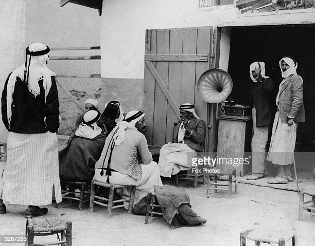 Arabs sit and listen to an oldfashioned phonograph at a cafe in old Jerusalem which has not yet installed the more modern radio