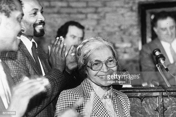 Civil rights leader Rosa Parks smiles while people gathered around her applaud at a ceremony held in her honor at the House of the Lord Church...