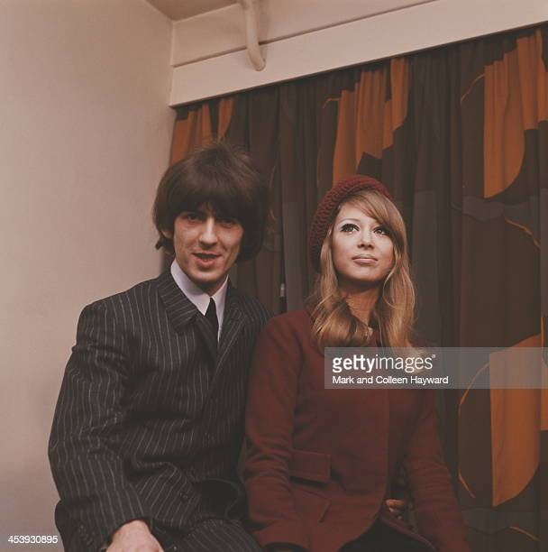 On the day after their wedding guitarist singer and songwriter George Harrison from The Beatles poses with his wife Patti Boyd at a press reception...