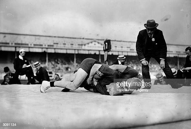 A referee closely watches the final of the Light Heavyweight GrecoRoman Wrestling event at the 1908 London Olympics Verner Weckman of Finland won the...