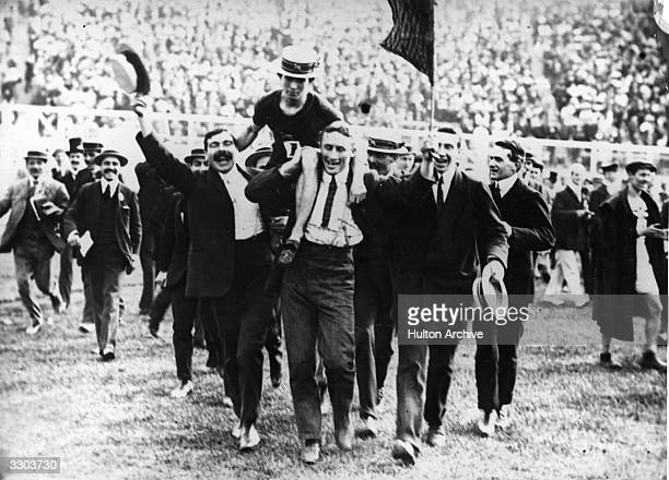 Reginald Walker of South Africa is carried from the track on supporters' shoulders after winning the final of the 100Metres at the 1908 London...